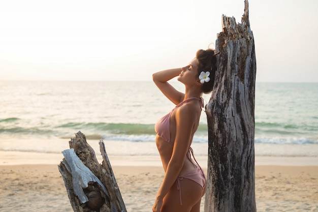 Женщина позирует возле коряги на пляже