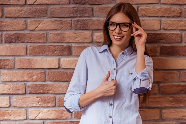 Woman is posing miling, touching eyeglasses and showing ok.