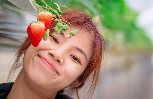 Woman is posing and smelling strawberry
