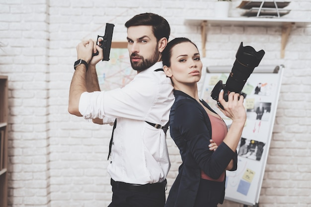 Woman is posing with camera, man is posing with gun.