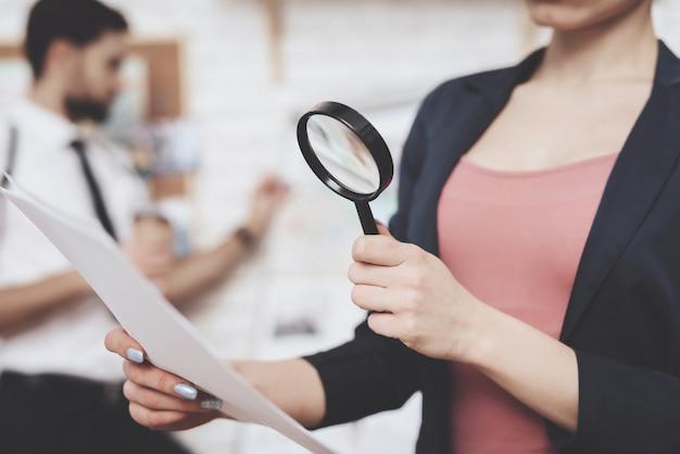 Женщина позирует с бумагой и увеличительное стекло.