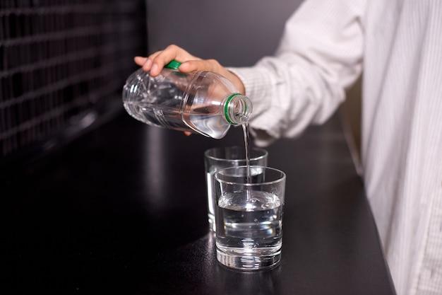 Женщина наливает воду из пластиковой бутылки в стакан на черном столе