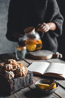 여자는 나무 태블릿에 신선한 자몽 조각과 뜨거운 차 한 잔을 따른다. 건강 음료, 에코, 비건.