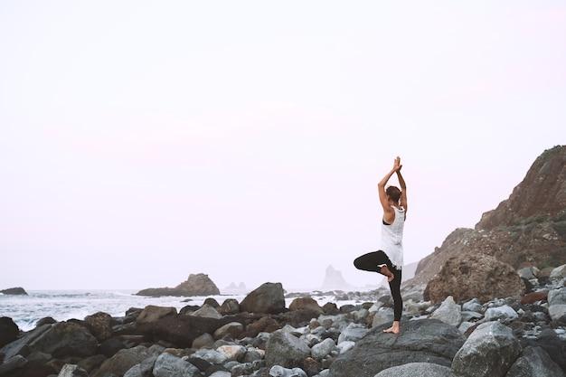 여자는 아름다운 야생 해변에서 요가와 명상을 연습하고 있다