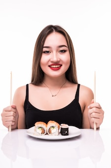Woman is preparing ready to eat taste sushi rolls using wooden chopsticks isolated on white