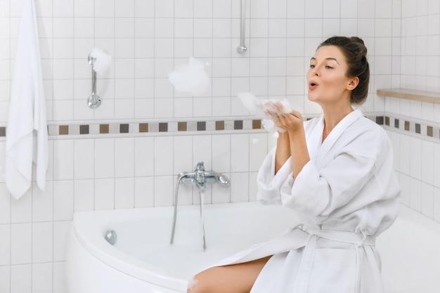 Женщина готовится принять ванну