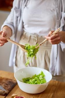 여자는 kitchem에서 야채 샐러드를 준비하고 있습니다.