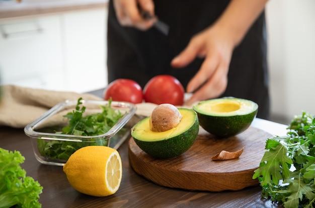 Женщина готовит овощной салат на кухне. здоровая пища. веганский салат. диета. готовить пищу.