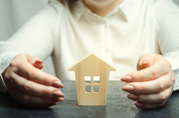 A woman is protecting a miniature wooden house.