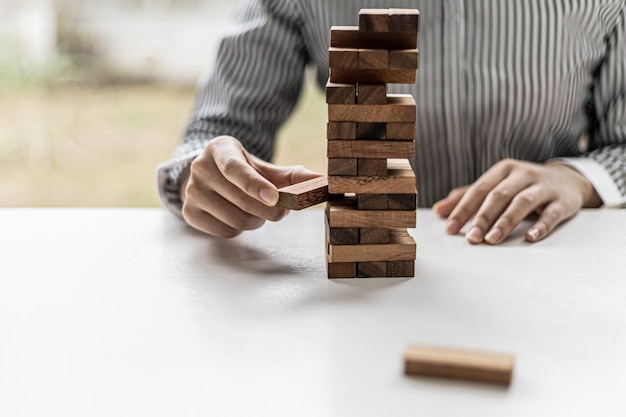 A woman is pulling a block of wood from a row and not breaking it down, like running a good business and solving problems. the concept of business management on risk.