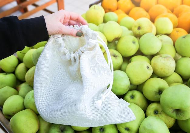 Женщина кладет яблоки в многоразовую хозяйственную сумку. нулевые отходы. экологически чистые и экологически чистые пакеты. холст и льняные ткани. сохраните понятие природы. нет одноразового использования пластика в супермаркетах.
