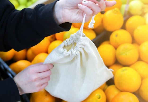 Женщина кладет апельсины в многоразовую хозяйственную сумку. нулевые отходы. экологически чистые и экологически чистые пакеты. холст и льняные ткани. сохраните понятие природы. нет одноразового использования пластика в супермаркетах.