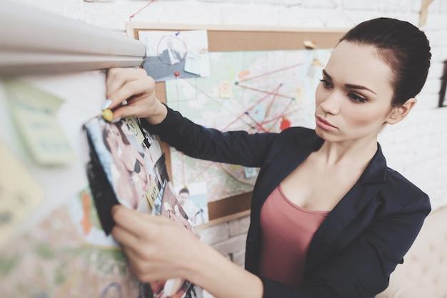 여자는 사무실에서 단서지도에 사진을 걸고있다.