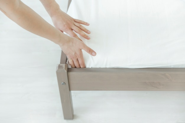 Женщина кладет на кровать покрывало или наматрасник или откладывает процесс чистки