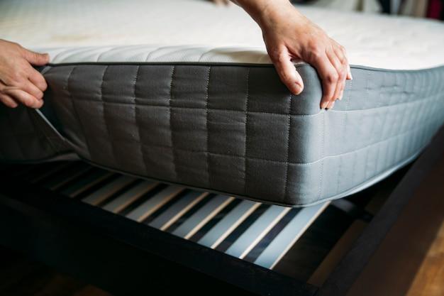 女性が寝具カバーやマットレスパッドをベッドに置いているか、掃除のために延期している