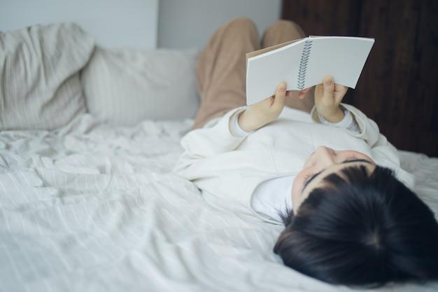Женщина читает книгу в спальне.