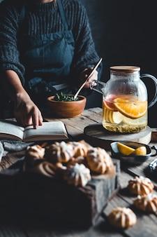 여자는 독서와 나무 태블릿에 신선한 자 몽과 뜨거운 차. 건강 음료, 에코, 비건.