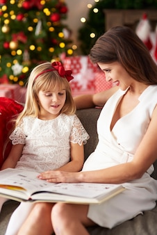 Woman is reading book with girl