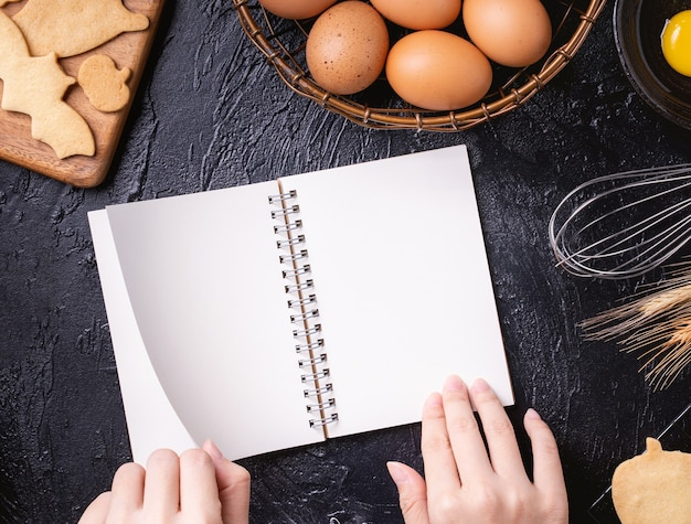 Woman is reading cookbook recipe of making halloween cookies with baking ingredients, design concept of cooking class, top view, flat lay, overhead.