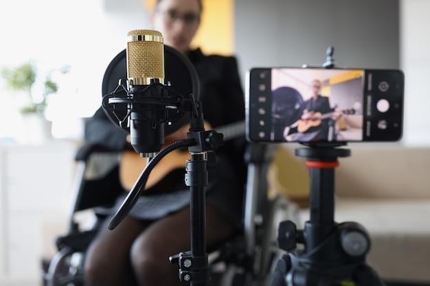 女性が車椅子の音楽レッスンに座ってギターを弾くビデオを録画しています