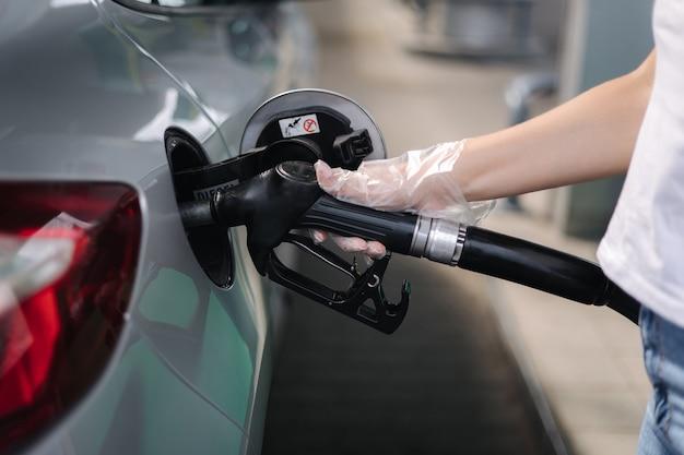 Женщина заправляет бензин бензин на бензоколонке в машине, используя топливо
