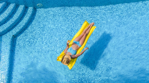 A woman is relaxing in the swimming pool on inflatable mattress