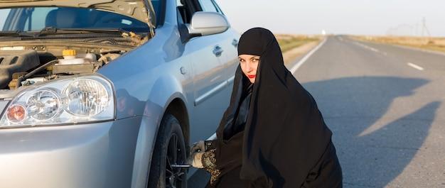 Женщина заменяет проколотое колесо автомобиля.