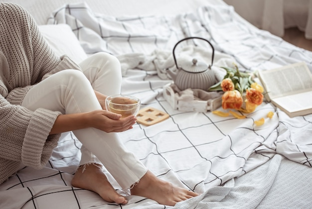 A woman is resting in bed with tea, a book and a bouquet of tulips. spring morning and weekend concept.