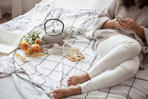 Una donna sta riposando a letto con un tè, un libro e un mazzo di tulipani. concetto di mattina e fine settimana di primavera.