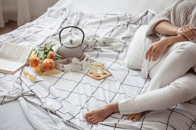 La donna sta riposando a letto con un tè, un libro e un mazzo di tulipani