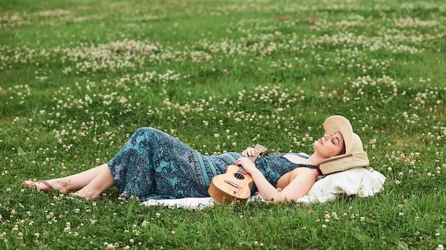 여자는 그녀의 손에 우쿨렐레를 들고 여름날 눈을 감고 풀밭에 누워 쉬고 있습니다. 광고를 위한 텍스트를 위한 장소입니다.
