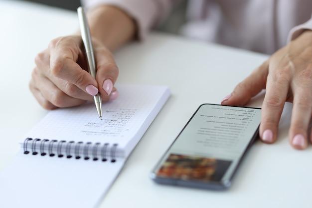 Женщина переписывает рецепт со смартфона в блокнот. интернет-рецепт приготовления концепции