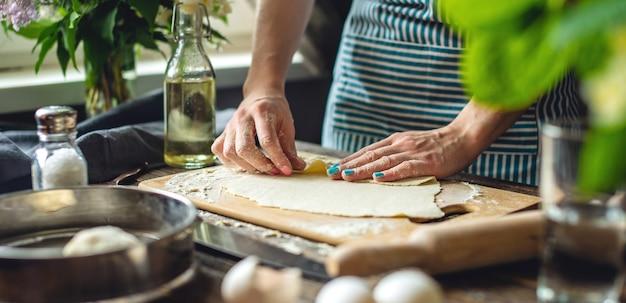 麺を作るために女性が生地を巻く