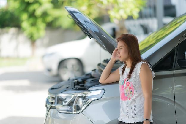 Женщина грустит из-за разбитой машины