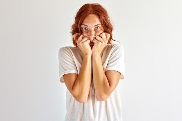 女性は何かに怖がり、ショックに立ち、顔を閉じ、何かを恐れます。白い背景に分離