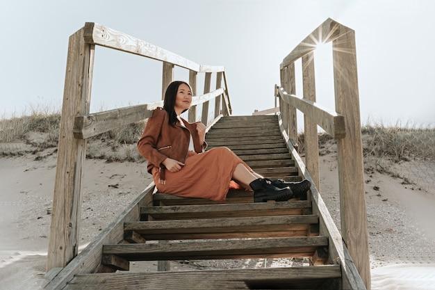Женщина сидит на деревянной лестнице на пляже, швеция, angelholm