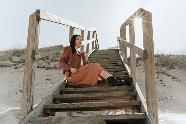 Woman is seating on wood stairs on beach, sweden, angelholm