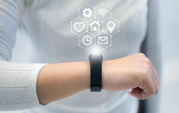 女性は革新的な技術を使用するためのスマートウォッチをセットアップしています。ミクストメディア、デジタル。