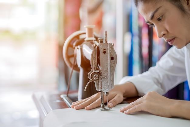 Женщина шьет на швейной машине дома, сидя на своем рабочем месте