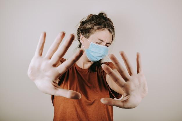女性は医療マスクにショックを受け、茶色のtシャツは白い壁に分離された彼女の手で停止信号を示しています。女性は家にいることを勧めます。