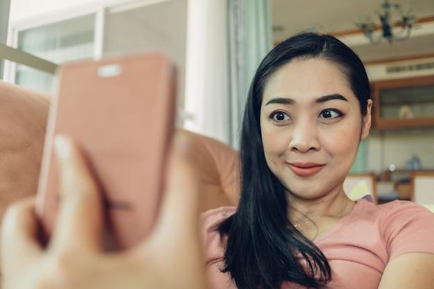 女性は彼女のスマートフォンでselfieを撮影しています。
