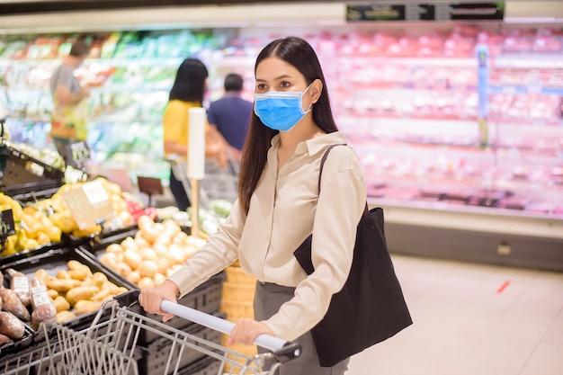 Женщина делает покупки в супермаркете с маской