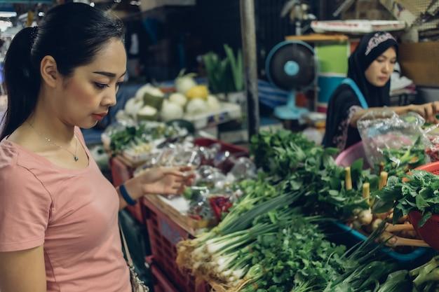 女性はタイの地元の新鮮な市場で買い物をしています。