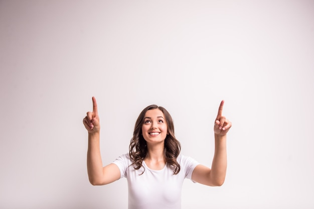 Woman is showing and pointing to side at blank copy space.