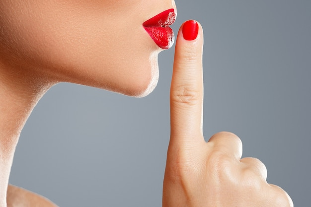Woman is showing shush or silence gesture