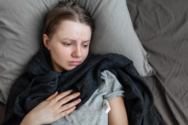 女性は自宅のベッドで病気です。胸の痛み。コロナウイルス(covid-19)冠状動脈ウイルス感染の症状には、息切れ、胸痛などがあります。一部の人にとっては、それは肺炎につながる可能性があります