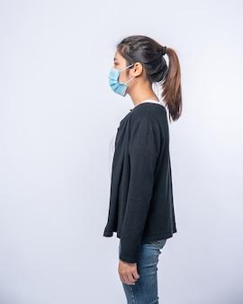 Una donna è malata in piedi con indosso una maschera. indossa un cappotto nero e jeans.