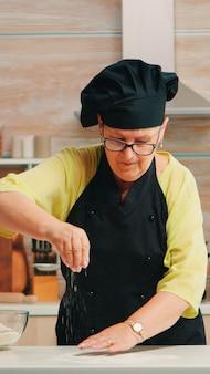 여자는 현대 부엌에서 나무 테이블에 밀가루를 체질하고 있습니다. 수제 케이크 뿌리기, 손으로 밀가루 체질하기 위해 원료를 준비하는 뼈가 있는 행복한 노인 베이커