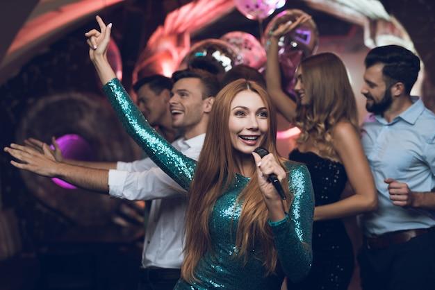Женщина поет песни со своими друзьями в караоке-клубе.