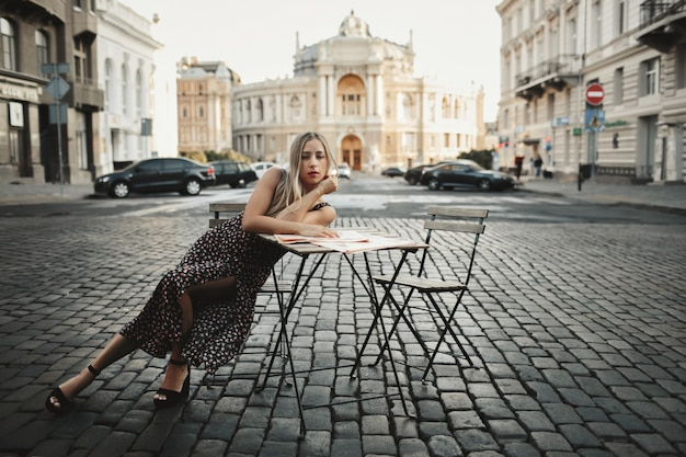 Woman is sitting alone near the coffee table on the street surrounded with old architectural buildings